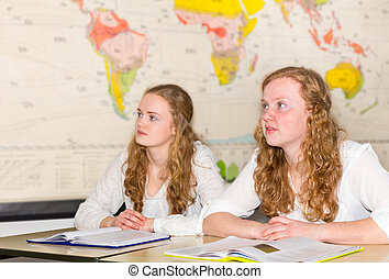 Two female  students in classroom with  world chart