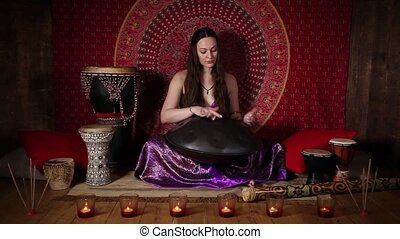 Woman playing hand pan - Young woman relaxing with hand pan...