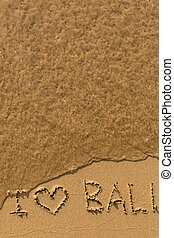 I love Bali - phrase written by hand on the beach with soft...