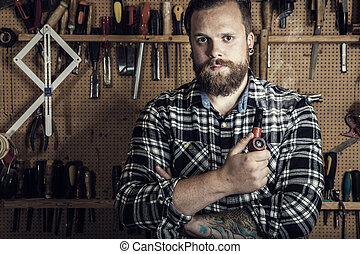 Environmental portrait of a man smoking pipe in wood...