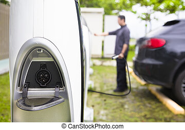 man operating Power supply station for electric car charging