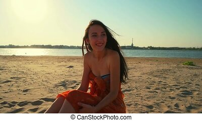 Free happy woman enjoying sunset. Beautiful woman sitting on sand in golden sunshine glow of sunset looking at camera enjoying peace, serenity in nature environment