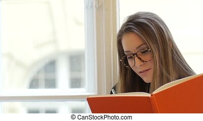 Portrait of young female student writing in the notepad with glasses sitting on the windowsill