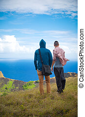 two men on the edge of the Rano Kau volcano, Easter island,...