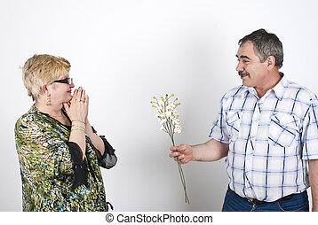 Husband offering flowers to his wife - Middle adult husband...