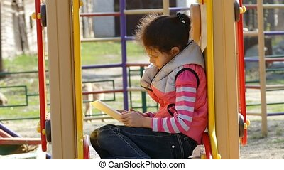 girl teen with the tablet online game on the playground...