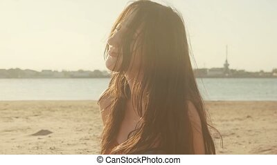 Young woman on beach wind tumble her long hair. She feels...