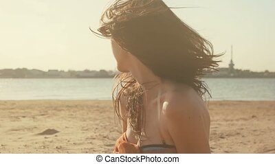 Portrait of the beautiful girl in sunset glow at summer beach, the wind fluttering her hair
