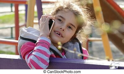 girl talking on a smartphone phone in the playground - girl...