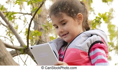 girl online game playing tablet sitting on tree