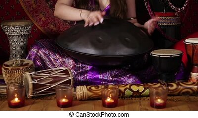 Wonderful sound of hand pan - Young adult woman playing hand...