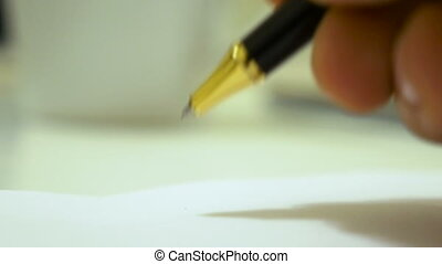 Close-up footage of a writing black ball pen on a paper.