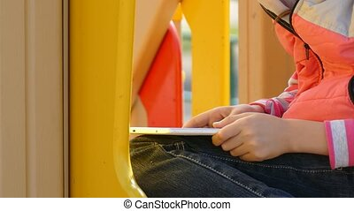 girl teen with the tablet online game on playground outddors...