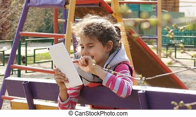girl doing selfie on white tablet on the playground