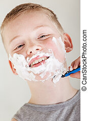 Solitary boy wearing gray shirt shaving his face - Head shot...