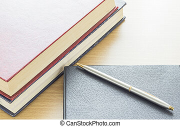 Pen put on notebook on deck wood