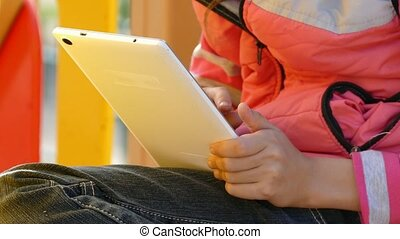 girl teen with tablet online game on playground outddors