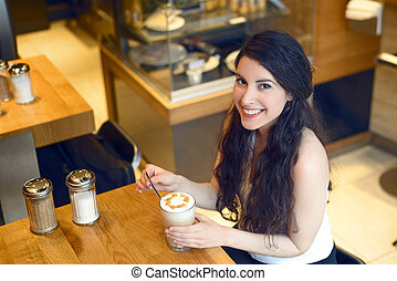Overhead view of smiling brunette woman with coffee