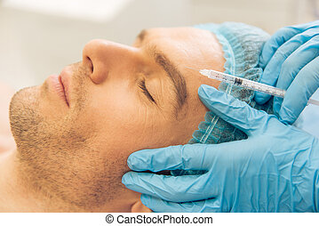 Man at the plastic surgeon - Side view of handsome young man...