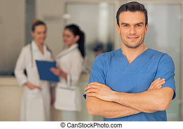 Handsome young doctor is looking at camera and smiling,...