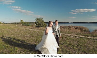 The groom and the bride run Aerial shot The Evening Lake -...