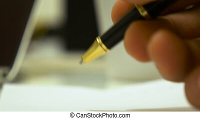 Male hand starts to write down a text on a paper by using a...