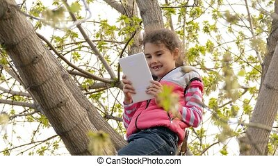 girl playing tablet sitting on the tree