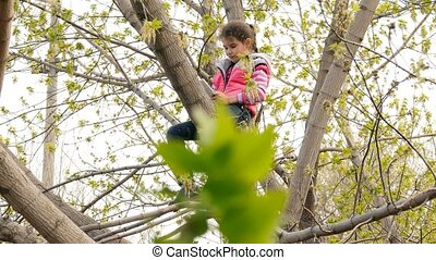 girl teen playing tablet online game sitting on tree - girl...