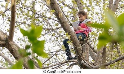 girl teen playing online game tablet sitting on tree