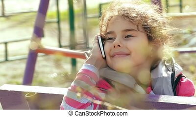 girl teen talking on smartphone phone in the playground -...