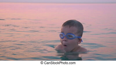 Boy Diving and Splashing in Sea Water - Little boy is...