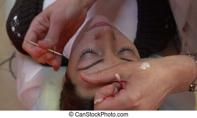 Makeup artist corrects woman's eyebrows - Beautician...