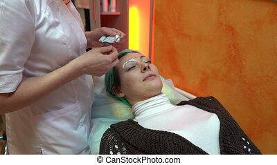 Beautician smears cream on the eyebrows - Makeup artist...