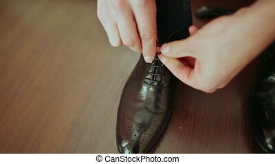 Man ties the laces on black shoes.