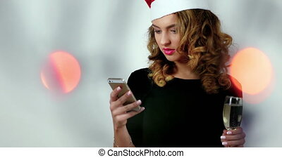 Female model is using a smarphone in a photo studio; girl wearing santa's hat and holding a glass of champagne; bokeh  illuminations on a front side;
