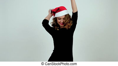 Attractive curly model is dancing in a santa's hat; girl...