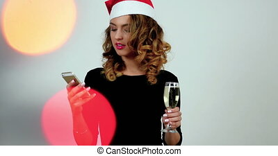 Handsome girl is making selfie in a studio by using smartphone; model wearing santa's hat and holding a glass of champagne; bokeh illuminations on a front side.