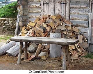 Pile of firewood next to hut cabin in mountain alps Alpe di...