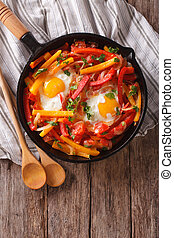 traditional Basque piperade with eggs close-up vertical top...