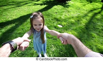 Little girl spinning in parents hands on sunset - Happy...