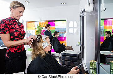 Woman Getting Her Hair Colored In Beauty Salon - Mature...