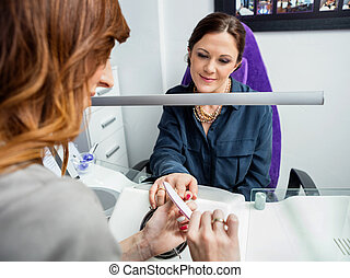 Cropped Image Of Manicurist Performing Manicure - Cropped...