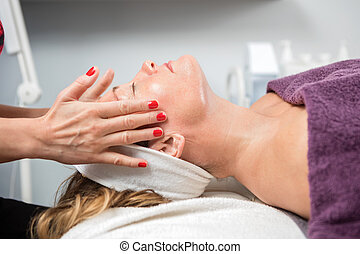 Woman Receiving Facial Massage In Beauty Parlor - Side view...