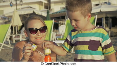 Mother and child blowing bubbles on the beach - Happy mother...