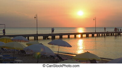 Pier on a Beach Resort at Sunset - People are walking along...