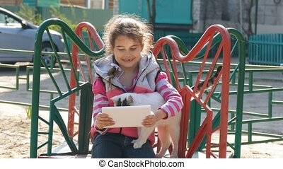 girl playing in the tablet on the playground with a cat