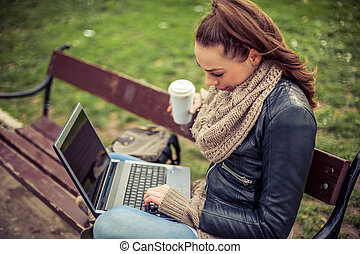 Young student Using laptop in park - Young female student...