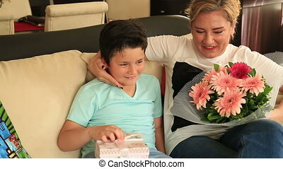 Cute boy offering gift to his mom - Happy mother receiving a...
