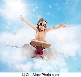 Young airman - Child with cardboard airplane in the sky