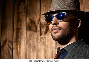 headwear style - Portrait of a handsome man by a wooden wall...
